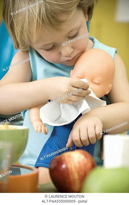 Little girl wiping baby doll's face with paper towel