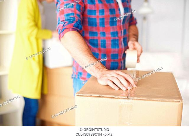 Young couple moving home, young man taping up cardboard box, mid section