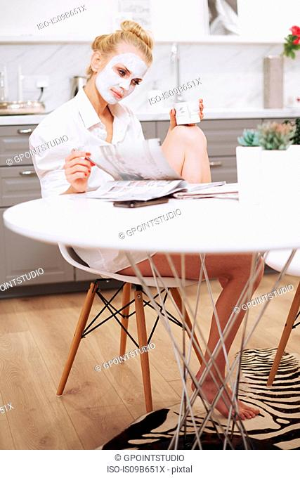Woman with face mask sitting at dining table reading magazine