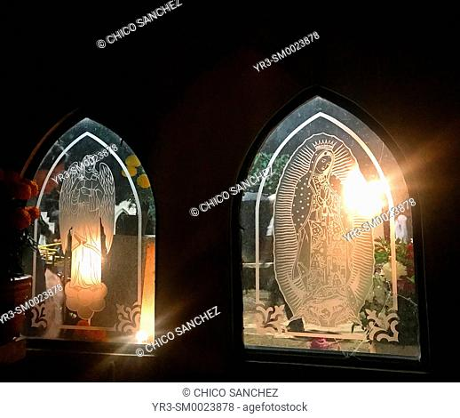 Candles illuminate a tomb decorated with images of Our Lady of Guadalupe and an angel during Day of the Dead celebrations in San Gregorio Atlapulco, Mexico City