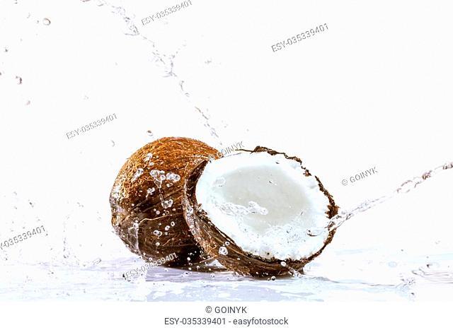 cracked coconut with big splash, isolated on white
