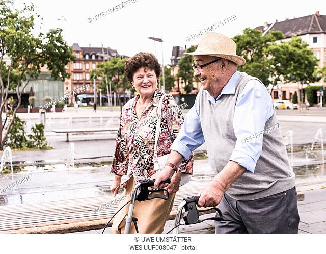 Senior man using wheeled walker for strolling with his wife
