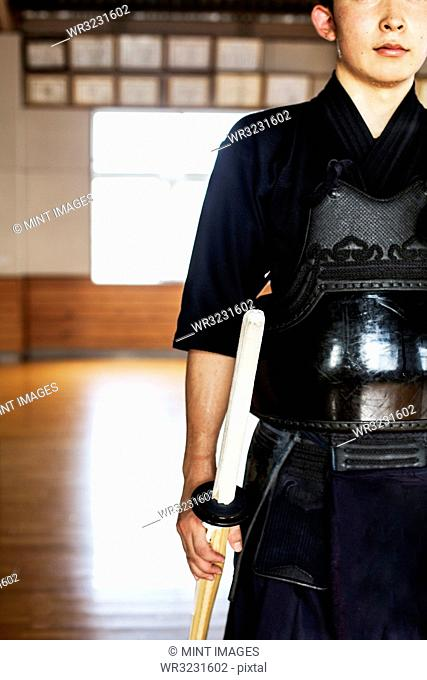 Male Japanese Kendo fighter standing in a gym, holding wood sword