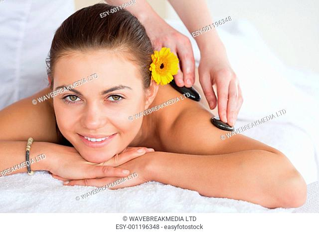 Smiling woman enjoying a hot stone massage with a flower on her ear
