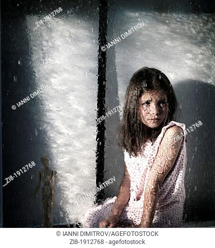Girl by the window,looking at the heavy rain outside