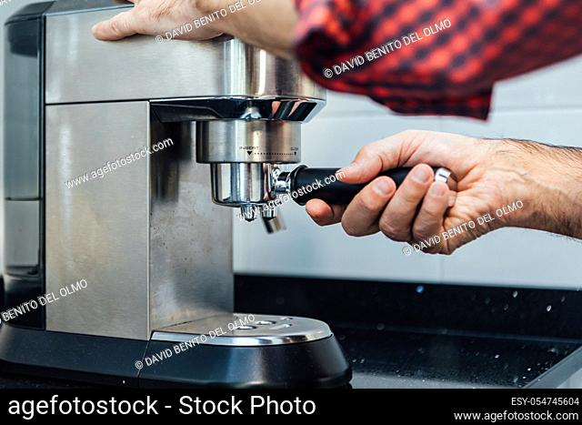 Detail of man's hands preparing an espresso
