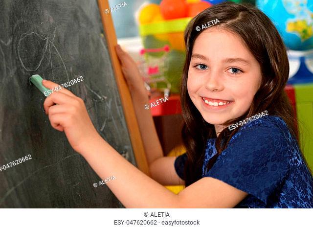 Portrait of a cute little girl drawing on chalkboard