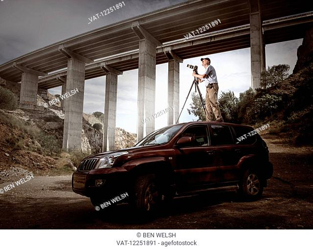 Photographer on top of a 4x4 wheel car; Benalmadena Costa, Malaga, Andalusia, Spain