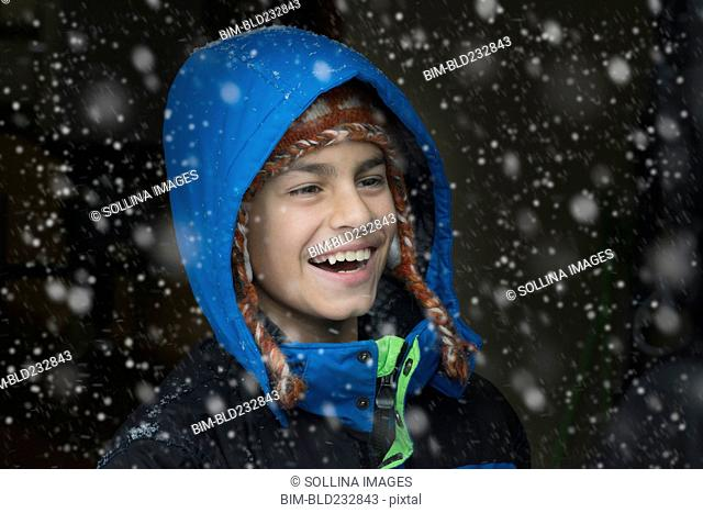 Mixed Race boy laughing in snow
