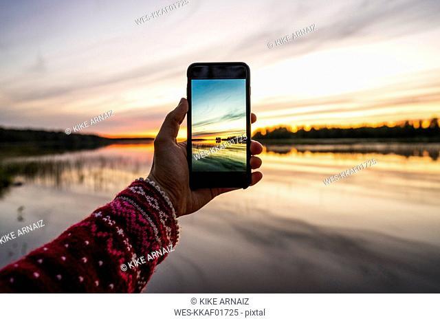 Finland, Kajaani, Person taking a smartphone picture of the sunset