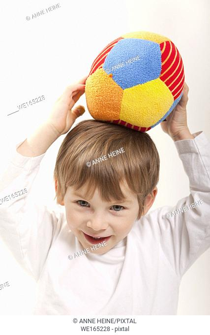 boy holding ball on head, white background, isolated