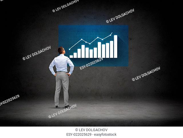 business, people, inspiration and strategy concept - businessman looking at chart over concrete room background from back