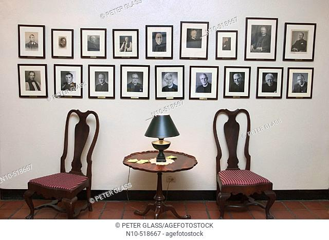 Chairs, table with a lamp, and portraits on the wall in a church lobby
