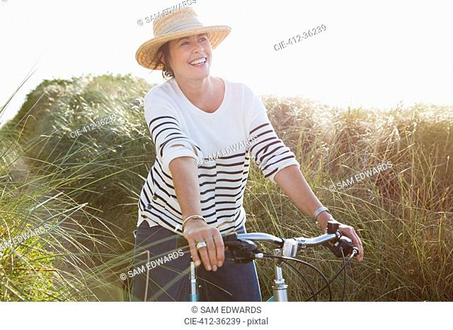 Smiling mature woman riding bicycle on sunny beach grass path