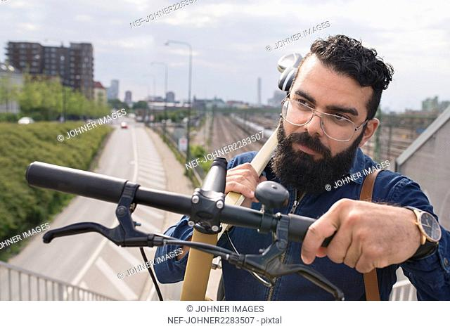 Bearded man carrying bicycle