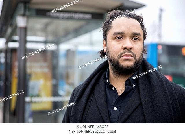 Young man standing on bus stop