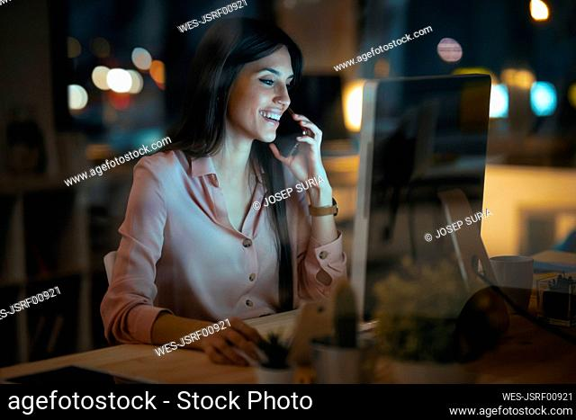 Laughing young woman on the phone working at desk in office