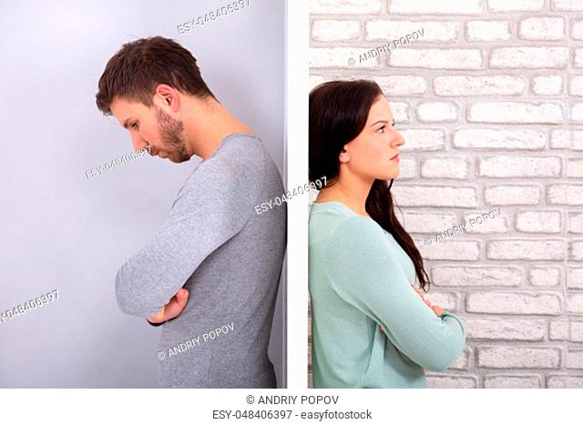 Side View Of Young Unhappy Couple Standing Back To Back At Home