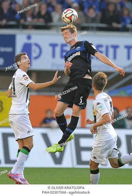 Paderborn's Patrick Ziegler (C) vies for the ball with Gladbach's Branimir Hrogota and Patrick Herrmann cheers after the German Bundesliga soccer match between...