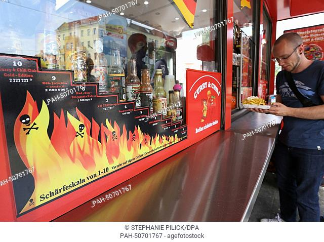 A young man orders a currywurst at the diner 'Curry & Chily' in Wedding in Berlin, Germany, 07 July 2014. The diner offers curry sausages in varying degrees of...