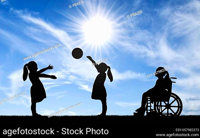 Silhouette of a disabled child girl in a wheelchair looking away as healthy children play in a ball outdoors. The concept of children with disabilities in a...