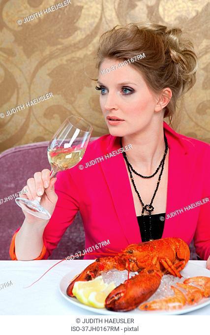 Woman having lobster in restaurant