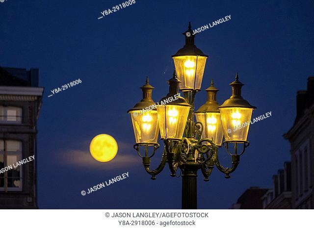 Full moon rising behind street lamps, Maastricht, Limburg, Netherlands