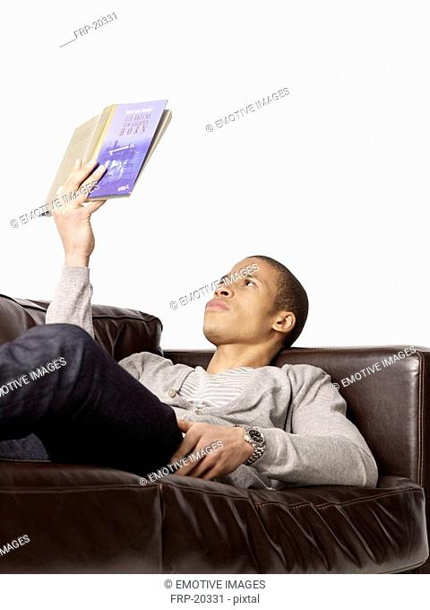 Man lying on couch reading book