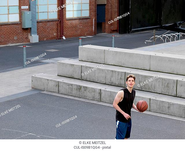 Young man playing basketball in outdoor court