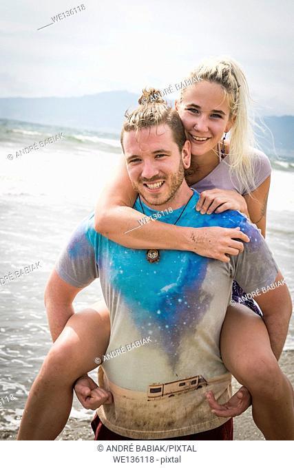 Young couple performing piggyback ride at a beach, Riviera Nayarit, Pacific Coast, Mexico
