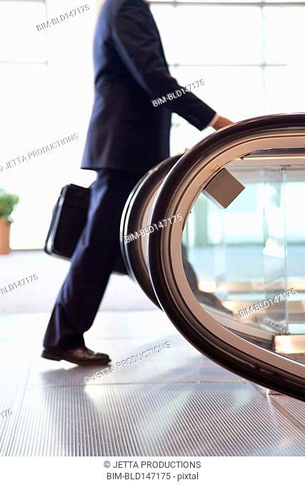 Caucasian businessman walking toward escalator