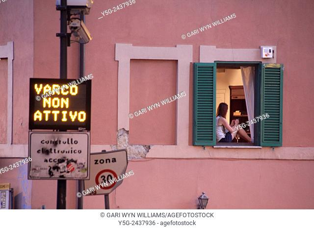 Young woman sitting in window in the trastevere district of Rome, Italy