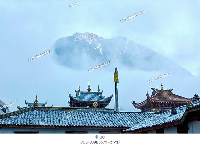 Roofs of Jingang Temple and misty mountain, Kangding, Sichuan, China