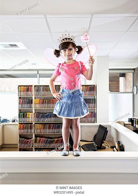 A young Caucasian girl dressed up as a fairy standing on a reception desk in a dental practice