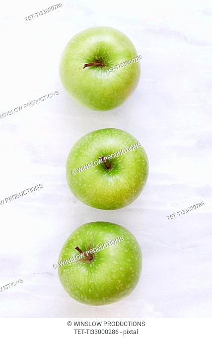 Overhead view of three apples on marble table