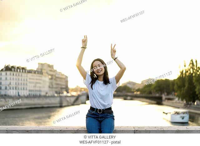 France, Paris, portrait of happy young woman at river Seine at sunset