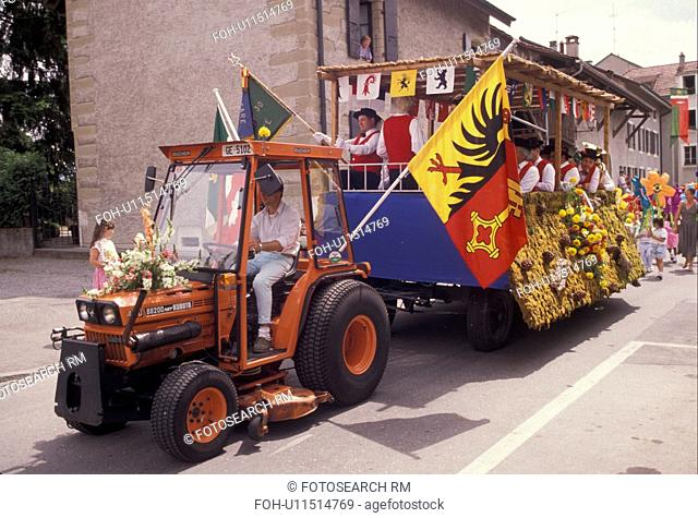 parade, celebration, Switzerland, Geneva, Europe, A band plays while riding on a float pulled by an orange tractor carrying the flag of Geneva during a...