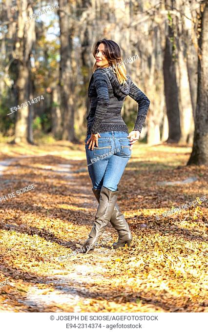 30 year old brunette woman looking over her shoulder at the camera wearing a sweater top, blue jeans and boots walking on a path outdoors in the autumn