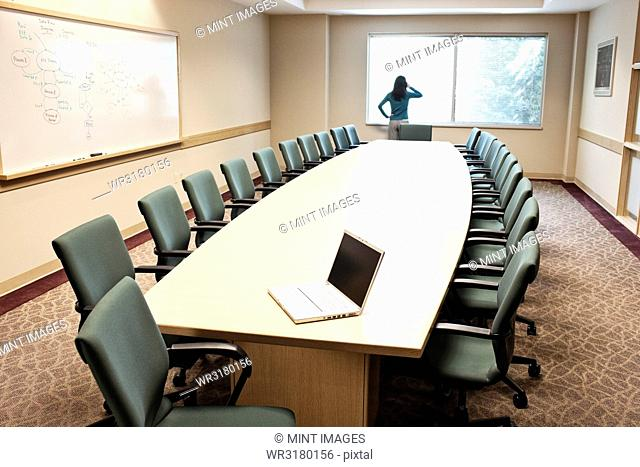 Woman using her phone at a window in a conference room