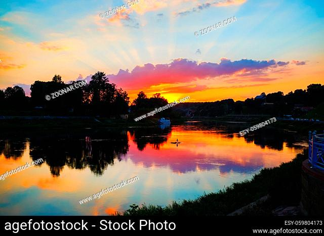 Sunset over the river. Bright colorful sky with clouds reflected in the water. Silhouettes of trees and bushes