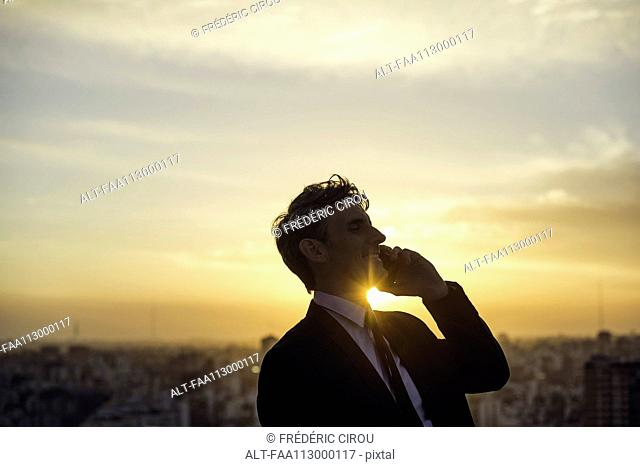 Man talking on cell phone back lit by setting sun