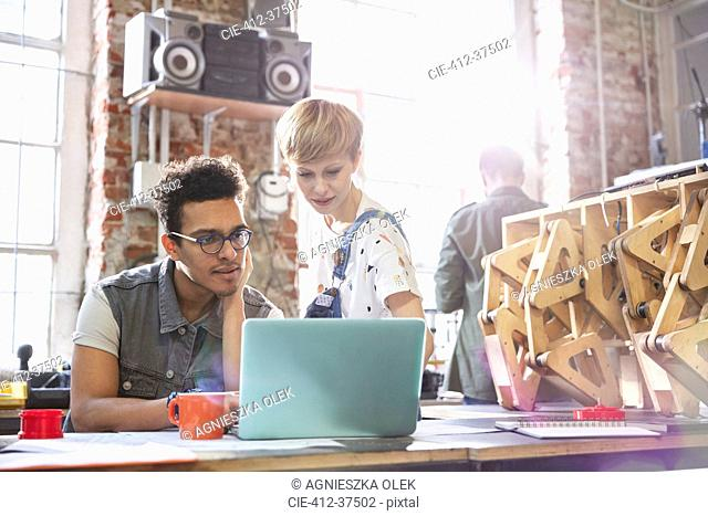 Serious, focused designers working at laptop in workshop