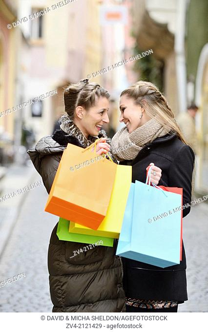 Two young woman with their bags from a shopping tour in a city in Germany