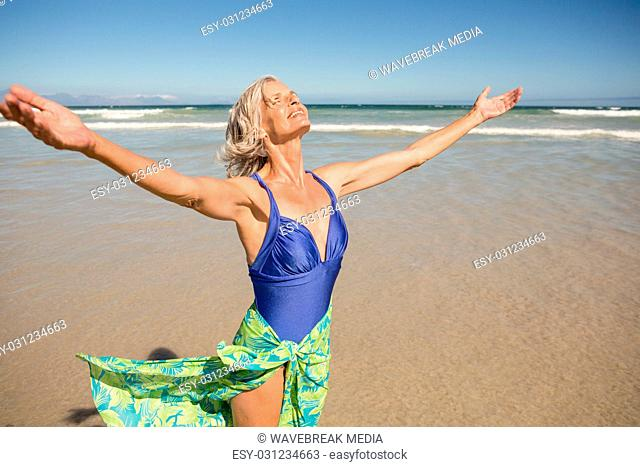 Happy senior woman with arms outstretched standing on shore