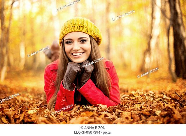 Smiling woman lying down on autumn leaves, Debica, Poland