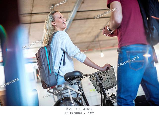 Young woman with bicycle greeting colleague in office