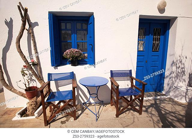 Chairs in front of a traditional Cyclades house with blue painted door and window in the old town Chora or Hora, Folegandros, Cyclades Islands, Greek Islands
