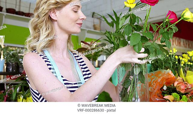 Female florist arranging roses in flower vase at flower shop