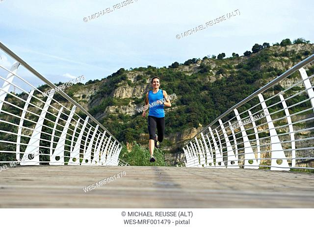 Italy, Trentino, woman running on footbridge near Lake Garda