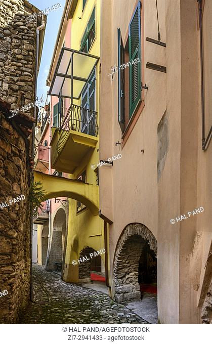 foreshortening of arched covered walkway under old picturesque bending houses , shot in bright late summer light at Varese Ligure, Genova, Liguria, Italy